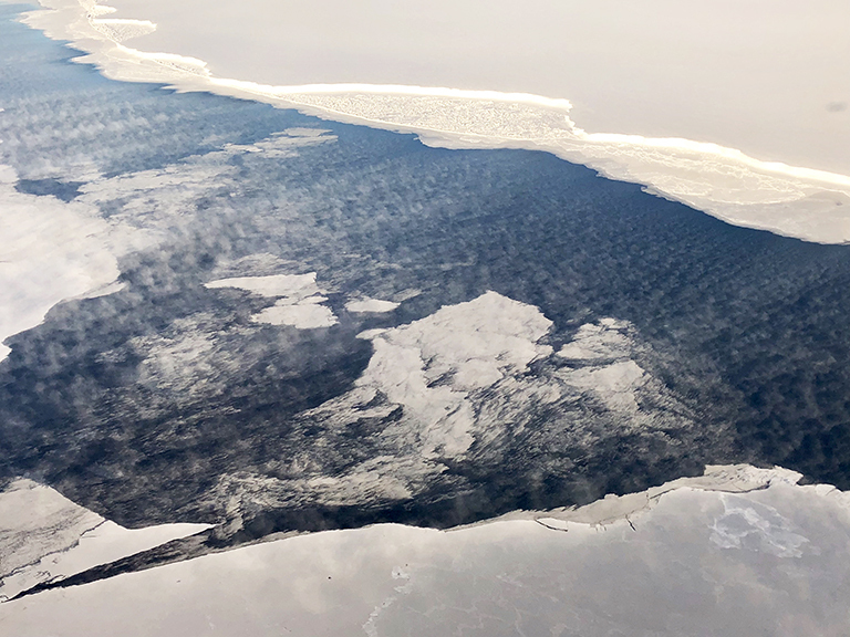 In this photo taken during a NASA IceBridge science flight off of the coast of Antarctica in fall of 2018, dry and cold winds blowing off the iceshelf over an opening in the sea ice (top of figure) cause evaporation from the ocean surface into the atmosphere, where low clouds form. Credit: Linette Boisvert